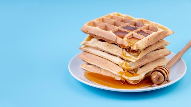 High angle of honey covered stacked waffles on plate with copy space