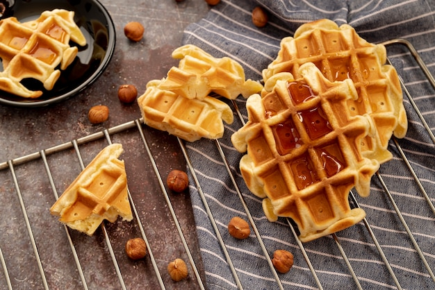 High angle of honey on top of waffles with hazelnuts
