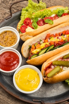 Hot dog ad angolo alto e contenitori per salse
