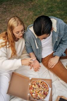 公園でピクニックをしているハイアングルの夫と妻