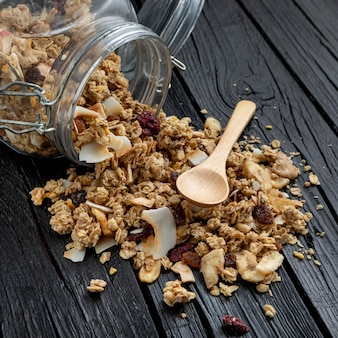 High angle of jar with breakfast cereals and spoon