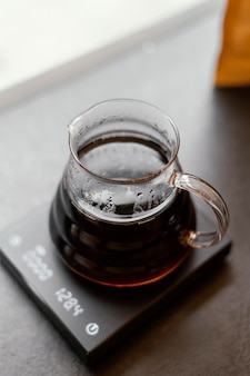 High angle of jug with coffee on scale in the coffee shop