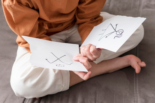 High angle kid holding broken drawing