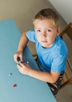High angle kid playing with lego