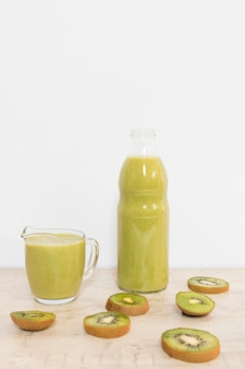 High angle kiwi smoothie in bottle and cup