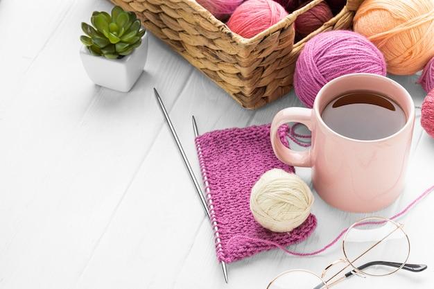 High angle of knitting set with tea and yarn