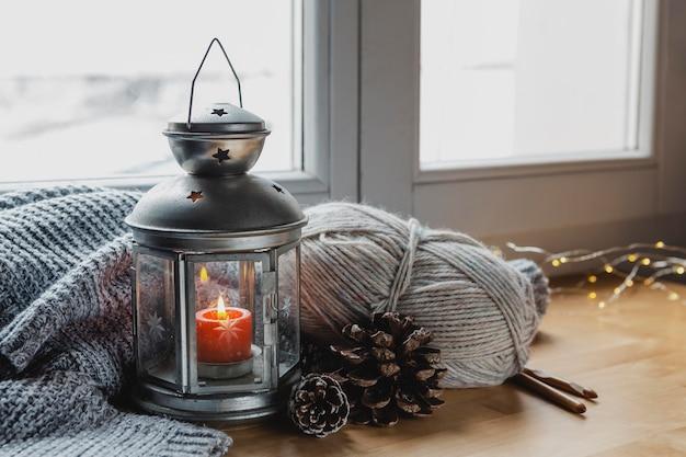 Lampada ad alto angolo e candela con pigne e filato