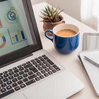 Высокий угол ноутбука и ассортимент кофе