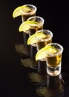 High angle line of gold tequila shots