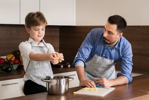 High angle little boy with father cooking