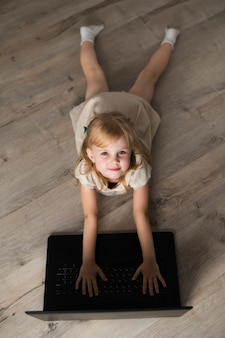 High angle little girl on floor looking at camera