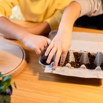 Alto angolo di bambini piccoli che piantano semi a casa