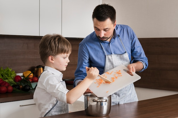 High angle little son helping dad to cook