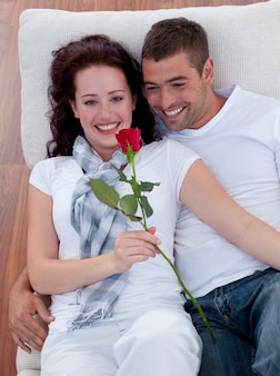 High angle of lovers on sofa with a rose