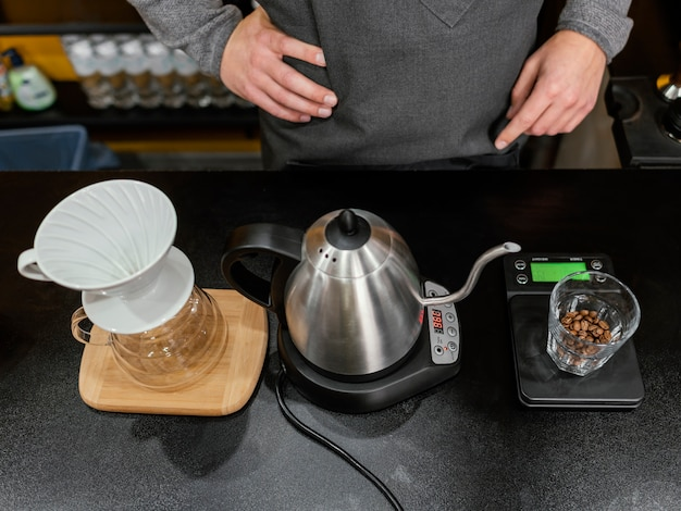 High angle of male barista preparing coffee with kettle and filter