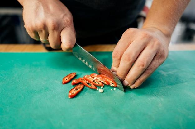 Alto angolo del cuoco unico maschio che taglia il peperoncino rosso