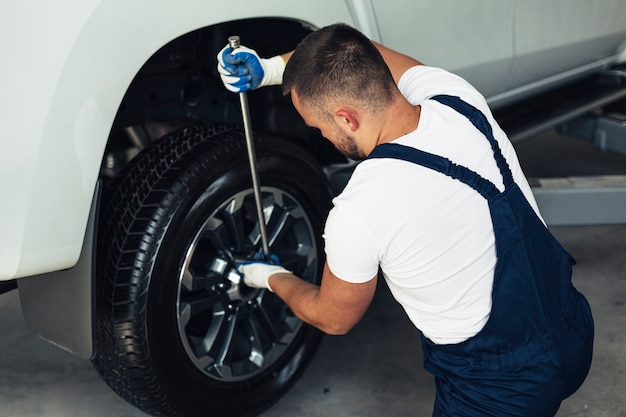 High angle male mechanic changing car wheels