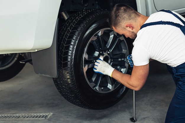 High angle male mechanic replacing wheel