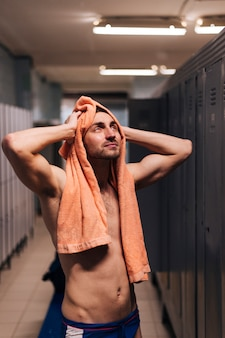 High angle male swimmer drying hair with towel