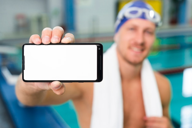 High angle male swimmer holding phone
