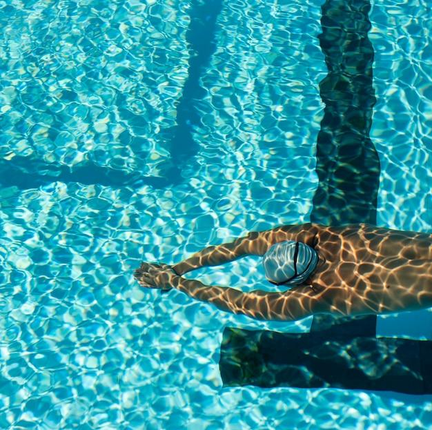 Alto angolo del nuotatore maschio che nuota nella piscina di acqua