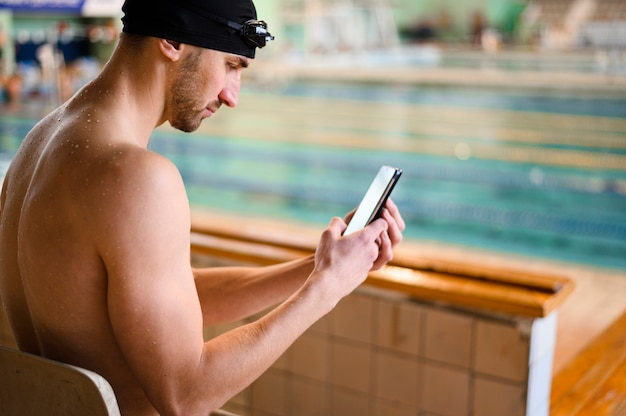 High angle male swimmer using phone