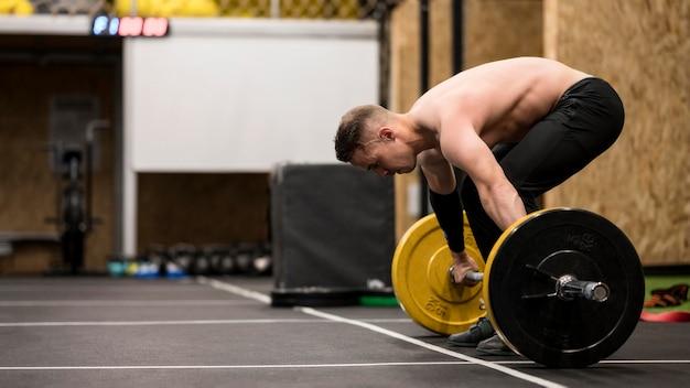 Allenamento maschile ad alto angolo con sollevamento pesi