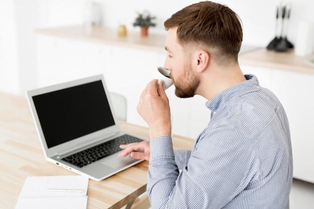 Человек высокого угла дома работая на компьтер-книжке