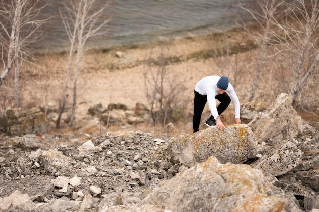 自然の中で岩を登る高角度の男