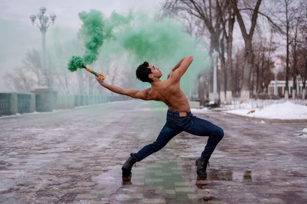 High angle man dancing ballet with color powder