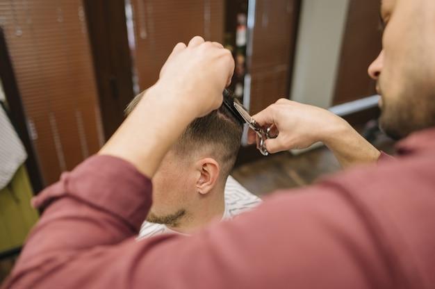 Alto angolo di uomo che ottiene un taglio di capelli