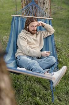 Alto angolo di uomo in amaca con smartphone