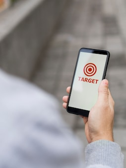 High angle of man holding smartphone with target on it
