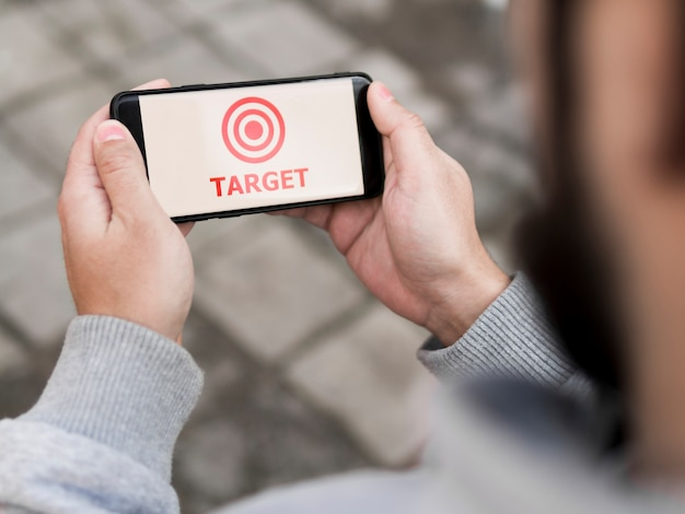 High angle of man holding smartphone with target
