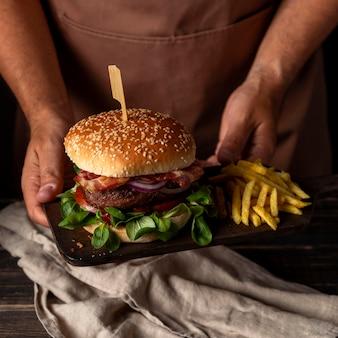 Человек под высоким углом держит поднос с гамбургером и картофелем фри