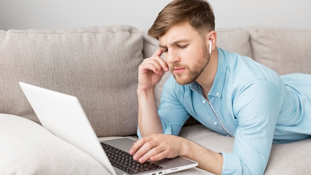 High angle man laid on couch with laptop