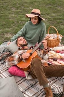 Человек под высоким углом лежит на коленях подруги и играет на гитаре