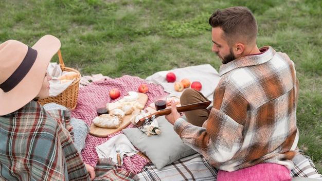 Высокий угол мужчина играет на гитаре для подруги