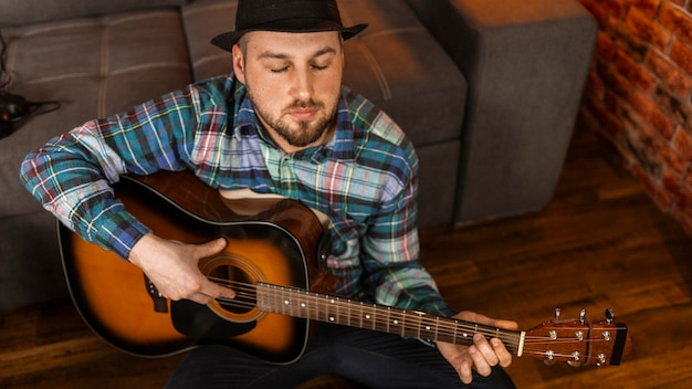 Uomo di alto angolo che gioca la chitarra