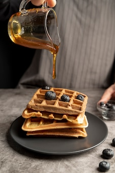High angle of man pouring syrup of stack of waffles
