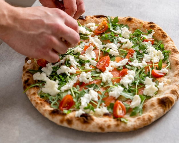 Мужчина под высоким углом кладет моцареллу на тесто для пиццы с ломтиками копченого лосося