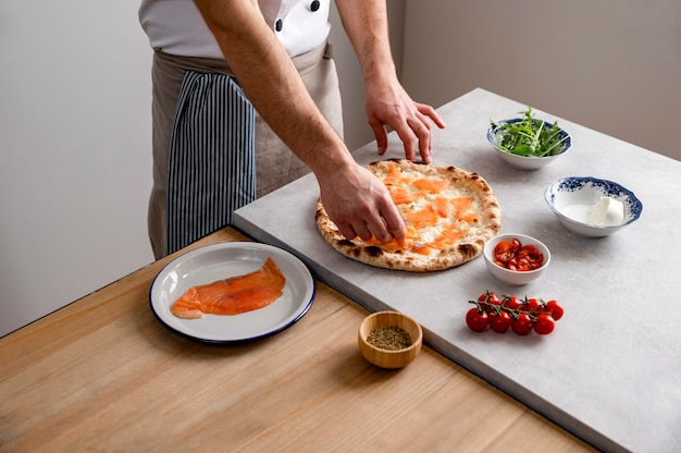 High angle man putting smoked salmon slices on baked pizza dough
