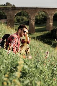 Uomo dell'angolo alto che si siede nel campo verde