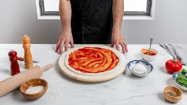 피자 반죽에 토마토 소스를 퍼뜨리는 높은 각도 남자