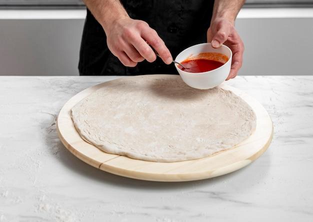 Человек под высоким углом намазывает томатный соус на тесто для пиццы