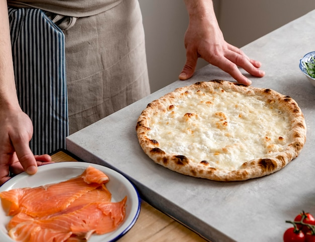 High angle man standing near baked pizza dough and smoked salmon slices