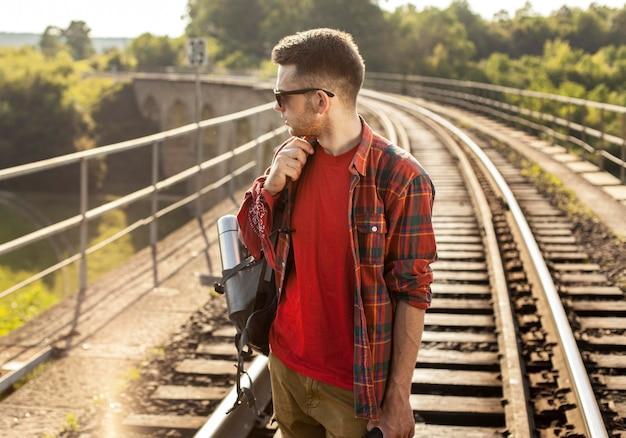 電車のレールにバックパックを持つハイアングル男