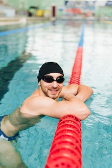 High angle man with swimming goggles and cap