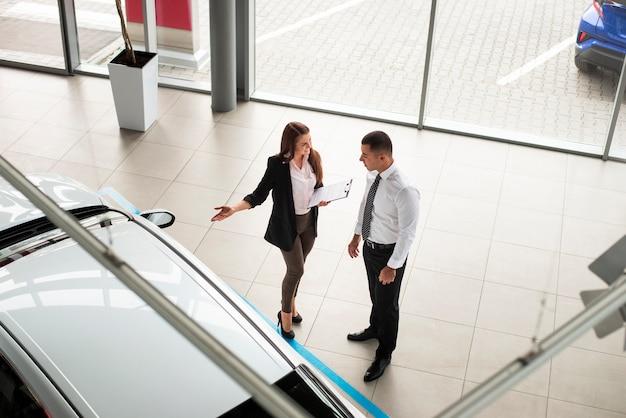 Uomo e donna dell'angolo alto al concessionario