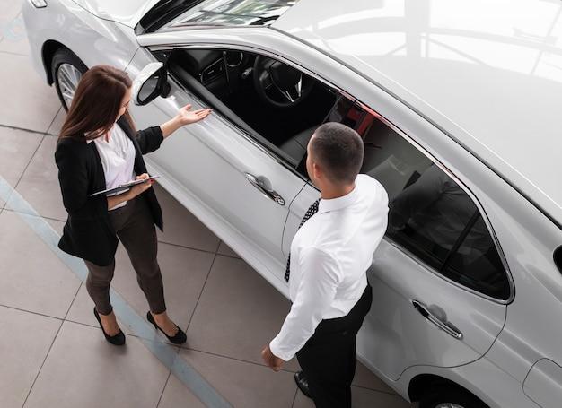 High angle man and woman at dealership